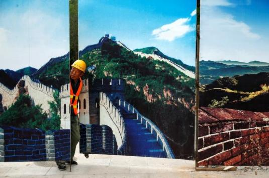 A worker looks through the fence of a construction site that is decorated with pictures of the Great Wall at Badaling